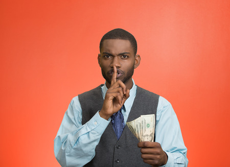Closeup portrait handsome corrupt guy businessman holding dollar bill in hand showing shhh sign finger to lips isolated red background. Bribery concept politics, business diplomacy. Face expression