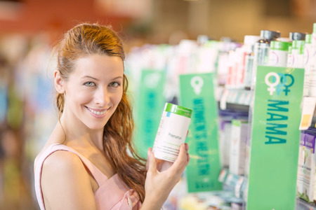 Photo pour Closeup portrait, happy, smiling beautiful young woman picking diet supplements isolated background grocery, pharmacy store shelves. Healthy lifestyle concept. Positive face expression emotion feeling - image libre de droit