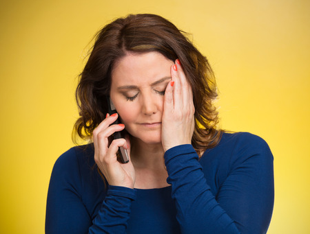 Young sad woman talking on mobile phone upset, depressed, unhappy, worried, isolated yellow background. Negative human emotions, facial expressions, feelings, life perception, reaction. Bad news