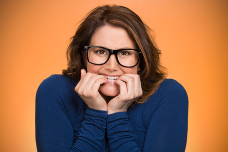Closeup portrait nervous, stressed young woman, employee student biting fingernails looking anxiously, craving for something isolated orange background. Human emotions, expression feeling body language