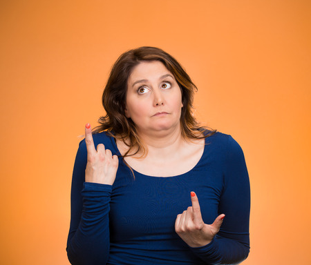 Closeup portrait confused young woman pointing in two different directions, not sure which way to go in life, isolated orange background. Negative emotions, facial expressions, feelings, body language