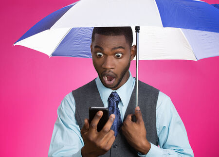 Closeup portrait shocked, surprised business man, corporate executive reading bad, breaking news on smart phone holding umbrella protected from rain isolated pink background. Face expression, emotion
