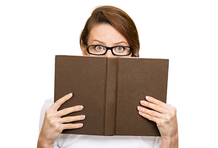 Closeup portrait woman with glasses hiding her face behind book, looking at camera suspicious, isolated white background. Education concept. Face expression, life perception. Girl holding book