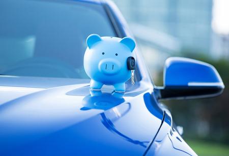 Closeup of piggy bank and key on car hood