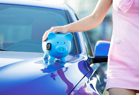 woman with a piggy bank, key on car hood