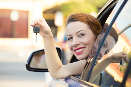 Closeup of happy, smiling, young attractive woman, buyer sitting in her new blue car showing keys