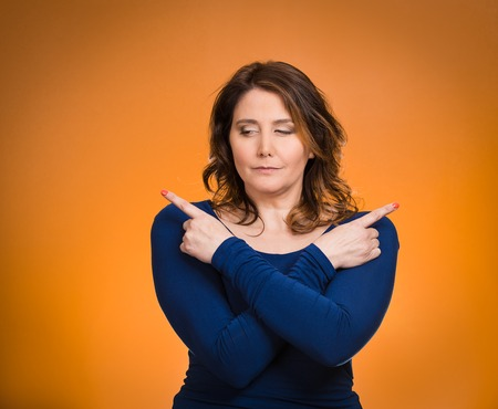 Portrait confused young woman pointing with fingers in two different directions, not sure which way to go in life, isolated orange background. Human emotions, facial expressions, feeling, body language