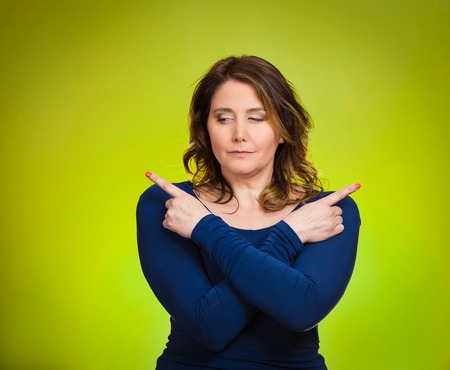 Portrait confused young woman pointing with fingers in two different directions, not sure which way to go in life, isolated green background. Human emotions, facial expressions, feeling, body language