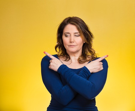 Portrait confused young woman pointing with fingers in two different directions, not sure which way to go in life, isolated yellow background. Human emotions, facial expressions, feeling, body language