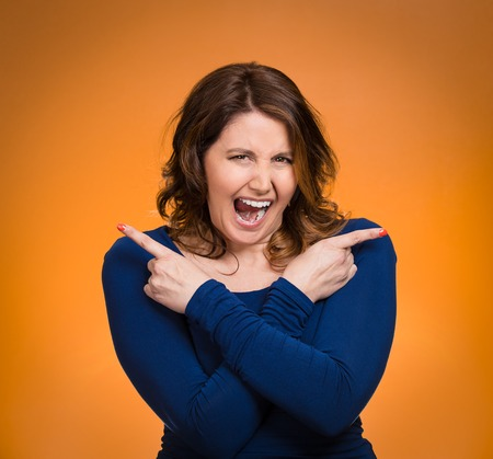 Portrait confused young woman pointing in two different directions, stressed, frustrated, screaming, overwhlemed, not sure which way to go in life isolated orange background. Negative emotion facial expression feeling body language