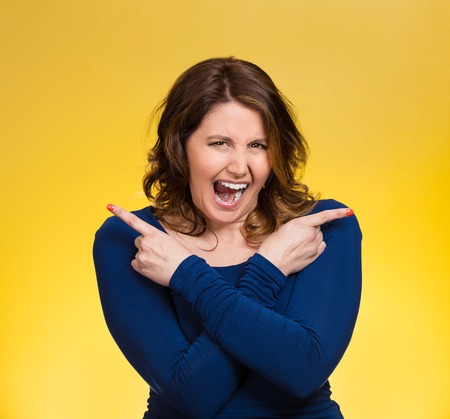 Portrait confused young woman pointing in two different directions, stressed, frustrated, screaming, overwhlemed, not sure which way to go in life isolated yellow background. Negative emotion facial expression feeling body language
