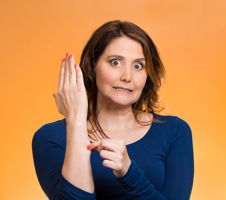 Portrait shocked, surprised woman pinching her arm skin, giving reality check gesture, is this dream, for real, isolated orange background. Human emotion, expression, feeling body language, perception