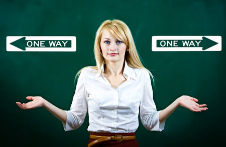 Portrait confused young woman shrugs shoulders, not sure which way, where go in life, isolated green background, with direction signs. Emotion, facial expression, feeling, reaction perception