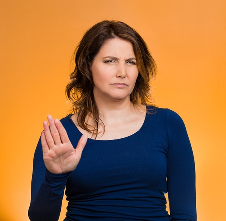 Closeup portrait middle aged, annoyed woman with bad attitude, giving talk to hand gesture with palm outward, isolated orange background.
