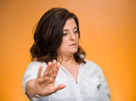 Offended. Portrait middle age grumpy woman with bad attitude giving talk to my hand gesture with palm outward, isolated orange background. Negative emotions, facial expression feelings, body language
