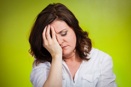 Depressed, gloomy. Closeup portrait unhappy middle age woman head on hand bothered by mistake having bad headache isolated green background. Negative human emotions facial expressions feelings