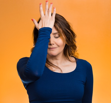 Portrait sad middle aged woman realizes mistake, regrets, slapping hand on head to say duh, isolated orange background. Negative emotions, facial expression, feelings, body language, reaction