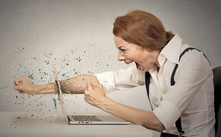 Angry, furious businesswoman throws a punch into computer, screaming. Negative human emotions, facial expressions, feelings, aggression, anger management issues