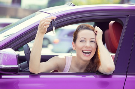 Closeup portrait happy, smiling, young attractive woman, buyer sitting in her new purple car showing keys isolated outside dealer, dealership lot office. Personal transportation, auto purchase concept
