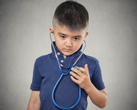 Closeup portrait child little boy listening to his heart with stethoscope isolated grey wall background. Children healthcare medical care, preventive medicine, self assessment concept. Face expression