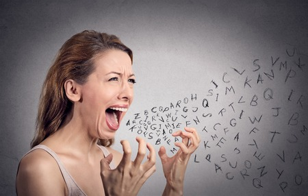 Foto de Side view portrait angry woman screaming, alphabet letters coming out of open mouth, isolated grey wall background. Negative human face expressions, emotion, reaction. Conflict, confrontation concept - Imagen libre de derechos
