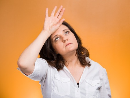 Closeup portrait annoyed tired middle aged woman placing back hand on forehead, tragedy of it all, woe is me, exaggerating isolated orange background. Negative emotion, facial expression, perception