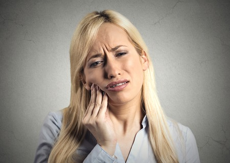 Closeup portrait young woman with sensitive tooth ache crown problem about to cry from pain touching outside mouth with hand, isolated grey wall background. Negative emotion facial expression feeling