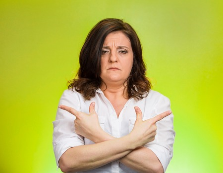 Closeup portrait confused middle aged woman pointing in two different directions, not sure which way to go in life isolated green background. Negative emotion facial expression feeling body language