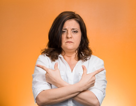 Closeup portrait confused middle aged woman pointing in two different directions, not sure which way to go in life isolated orange background. Negative emotion facial expression feeling body language
