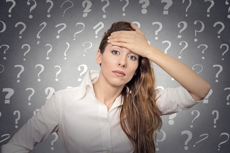 Portrait stressed woman with headache has many questions isolated grey wall background with question marks.