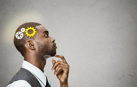 Foto de Side view portrait young business man thinking deciding finger on chin looking up gear mechanism over head isolated grey wall background copy space. - Imagen libre de derechos