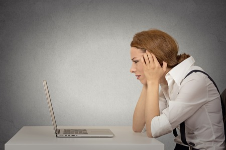 Photo pour Portrait stressed young unhappy business woman working on laptop siting at desk isolated grey wall office background. Long working hours, complicated software concept. Negative face expression emotion - image libre de droit