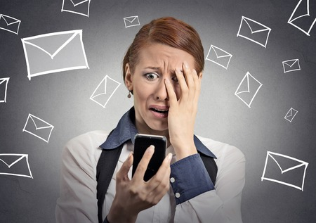 Upset stressed woman holding cellphone disgusted shocked with message she received isolated grey background. Funny looking human face expression emotion feeling reaction life perception body language