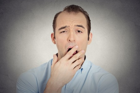 Closeup portrait headshot sleepy young businessman funny guy placing hand on mouth yawning looking at camera isolated grey wall background. Negative human emotion face expression feeling body language