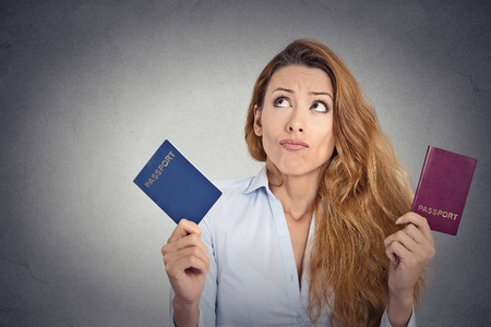 Portrait young woman holding two passports confused face expression isolated on grey wall background