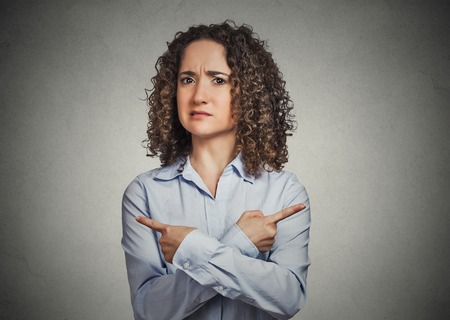 Indecision confusion. Portrait confused young woman pointing in two different directions not sure which way to go isolated grey background. Negative emotion facial expression feeling body language