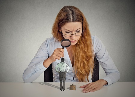 Curious corporate businesswoman skeptically meeting looking at small employee standing on table through magnifying glass isolated grey office wall background. Human face expression attitude perception