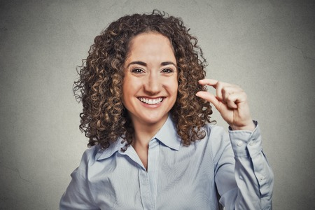 Closeup portrait, funny young curly brown hair woman showing small amount gesture with hand fingers isolated grey background. Human emotion facial expression feelings, body language, signs, symbols