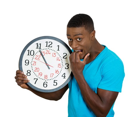 Photo pour Closeup portrait funny looking man student holding wall clock, stressed biting fingernails pressured by lack, running out of time, late meeting, interview, appointment isolated white background. Emotion - image libre de droit