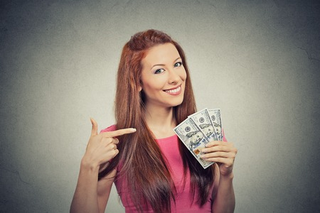 Closeup portrait super happy excited successful young business woman holding money dollar bills in hand isolated grey wall background. Positive emotion facial expression feeling. Financial reward