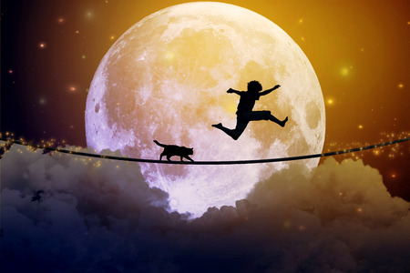 Foto de Happy boy teenager and cat jumping with balloon on a tight rope above clouds with moonlight moon background. Happiness care free concept. - Imagen libre de derechos