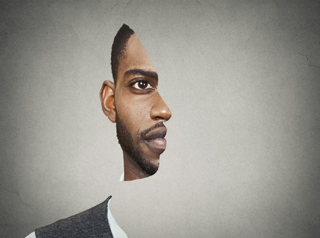 Foto de Optical illusion surrealistic portrait front with cut out profile of a young man isolated on grey wall background - Imagen libre de derechos
