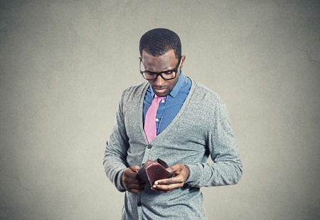 Photo for Young man looking into his empty wallet has no money - Royalty Free Image