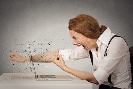 Photo pour Side profile angry furious businesswoman throws a punch into computer, screaming. Negative human emotions, facial expressions, feelings, aggression, anger management issues concept - image libre de droit