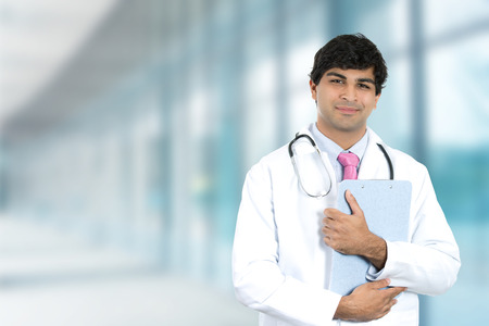 Portrait of friendly smiling male doctor with clipboard standing in hospital hallway clinic isolated on office windows background
