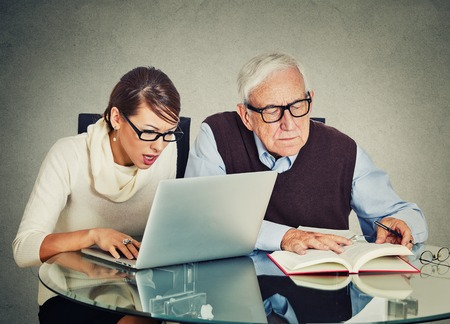 Portrait young woman working on laptop and older senior mature grandpa man reading from book on table isolated gray wall background. Generation differences and gap technology concept