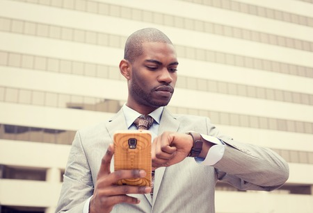 portrait young businessman texting on mobile phone and looking at his watch isolated on outdoor background of corporate building windows