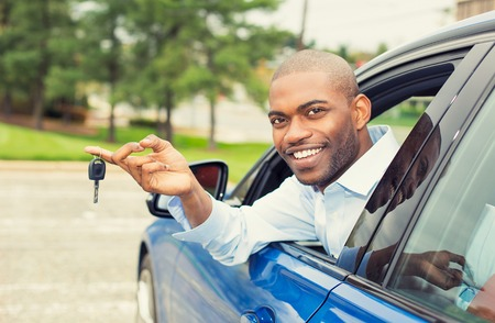 Closeup portrait happy, smiling, young man, buyer sitting in his new blue car showing keys isolated outside dealer, dealership lot, office. Personal transportation, auto purchase concept