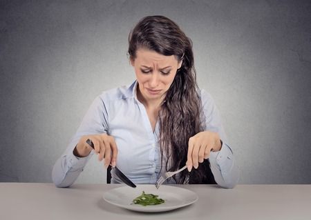 Young woman tired of diet restrictions eating green salad sitting at table isolated grey wall background. Human face expression emotion. Nutrition concept