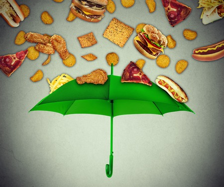 Bad diet protection food concept with group of greasy fatty fast food falling down like rain and green umbrella stopping unhealthy food as metaphor for poor nutrition eating habits